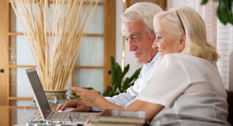 Older couple looking at a laptop screen and pointing